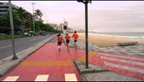 Slow pan of three joggers jogging from a path going towards the road in Rio de Janeiro, Brazil