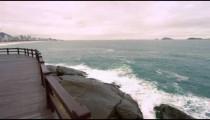 Slow motion tracking shot of splashing waves on rocks under a bridge in Rio de Janeiro, Brazil