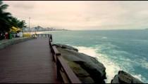Slow motion dolly shot of a wooden bridge over rocks and splashing waves in Rio de Janeiro, Brazil