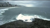Slow pan of waves splashing on rocks along the coast in Rio de Janeiro, Brazil