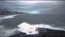 Slow pan of big waves crashing onto the rocks at the beach in Rio de Janeiro, Brazil