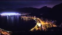 Pan of metropolis and lagoon in Rio de Janeiro, Brazil at night