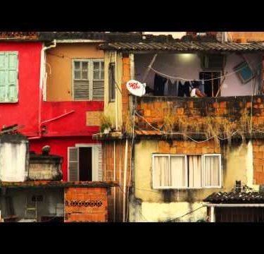 Slow motion static footage of a colorful, run-down favela and a woman