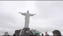 Slow motion pan of tourists standing at the base of Rio's Christ the Redeemer statue