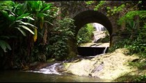 Tracking shot of a scenic stream flowing underneath an arched bridge.