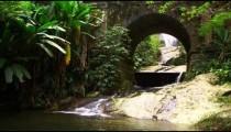 Stream flowing underneath arched bridge.