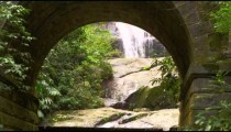 Tracking shot of a waterfall through a sone arch.