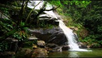 Tracking shot of a jungle waterfall cascading into a deep green pool.