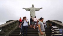 Slow motion tilt of tourists at the statue of Christ in Rio