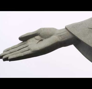Pan of the sleeve to the right hand of Rio's monumental sculpture of Christ the Redeemer.