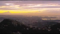 Pan over yellow and pink sunset above Rio de Janeiro cityscape.