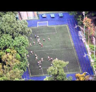 Bird's eye footage of people running across football field