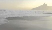 Pan of waves and people on Ipanema beach