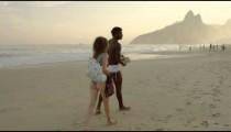 RIO DE JANEIRO-JUNE 16: Young couple walks along Ipanema beach on June 16, 2013 in Rio de Janeiro.