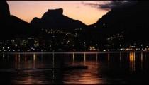 Person rowing on shoreline of Rio de Janeiro during sunset
