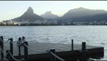 Slow-mo, tracking shot of a trio of girls sitting on a floating dock across from Ipanema in Lagoa