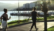 Slow-motion tracking shot of people walking on a path beside Lagoa.
