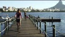 Women biking off small lake pier