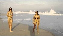 Slow motion, tracking shot of two girls on Ipanema beach in bikinis wearing sunglasses