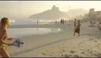 Slow motion shot of a couple playing tennis on Ipanema beach at dusk