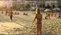 Slow motion, 180 tracking shot following a couple after playing a game of tennis on Ipanema beach