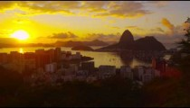 Lens flare and large setting sun tracking shot over Atlantic Ocean and Botafogo Bay.