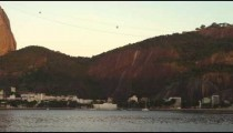 Pan across Guanabara Bay in Rio with a sailboat and Sugarloaf Mountain in the distance.