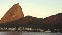Pan of Sugarloaf Mountain with cable cars asending and descending.