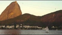 Static shot of a sailboat on Guanabara Bay with Sugarloaf Mountain in the distance.