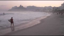 Slow motion pan of surfer at sunset along sandy beach with mountains and city in the background
