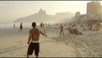 A couple playing tennis on Ipanema beach together