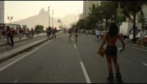 Slow motion tracking shot of a Brazilian girl rollerblading down Avenida Vieira Souto