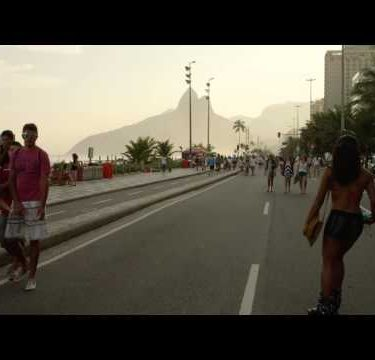Slow motion tracking shot of a Brazilian girl rollerblading down Avenida Vieira Souto at dusk