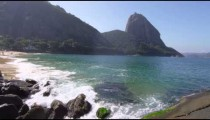 Slow motion rack-focus of waves washing up on Red Beach in Rio.