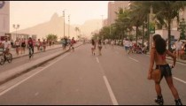 Slow motion tracking shot of Brazilian girl rollerblading down Avenida Vieira Souto at dusk.