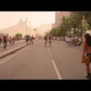 Slow motion tracking shot of Brazilian girl rollerblading down Avenida Vieira Souto at dusk.