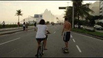 Slow-mo tracking shot of a girl on bicycle & a guy on skateboard heading down Avenida Vieira Souto