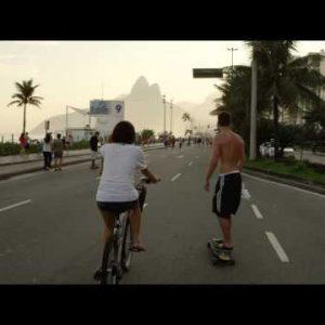 Slow-mo tracking shot of a girl on bicycle & a guy on skateboard heading down Avenida Vieira Souto