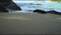 Slow motion of the sand at Rio's Red Beach with waves beyond.