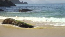 Slow motion of waves swirling around a boulder at Rio's Red Beach.