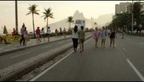 Slow motion tracking shot of a blond girl walking her dog down Avenida Vieira Souto