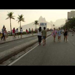 Slow motion tracking shot of a blond girl walking her dog down Avenida Vieira Souto