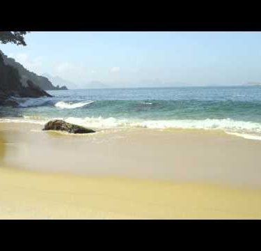 Slow motion of waves ebbing and flowing around a boulder on the sand at Rio's Red Beach.