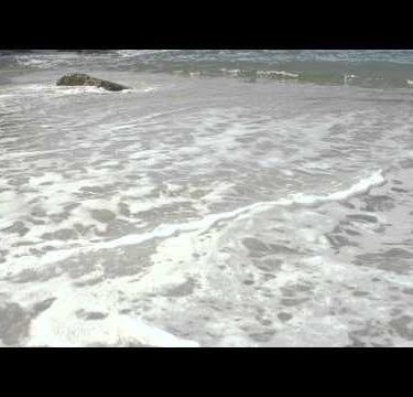 Slow motion of waves ebbing and flowing on a Rio beach.