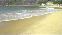 Slow motion pan of waves washing up on a Rio beach.
