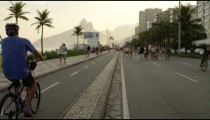 Slow motion tracking shot of a man riding his bike down Avenida Vieira Souto