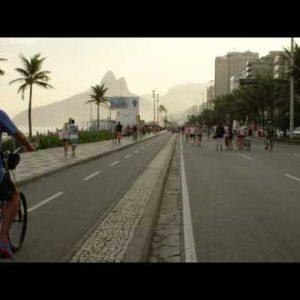 Slow motion tracking shot of a man riding his bike down Avenida Vieira Souto