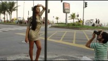 Slow motion, tracking shot of a model posing at an intersection on the Avenida Vieira Souto