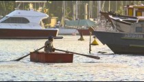 Slow motion of a man rowing a boat amidst a variety of larger craft.