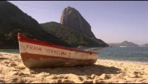 Slow motion pan of a fishing skiff on Red Beach in Rio.